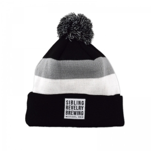 Sibling Revelry pom beanie with woven label patch.